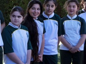 Girls standing outside in their sports uniforms.